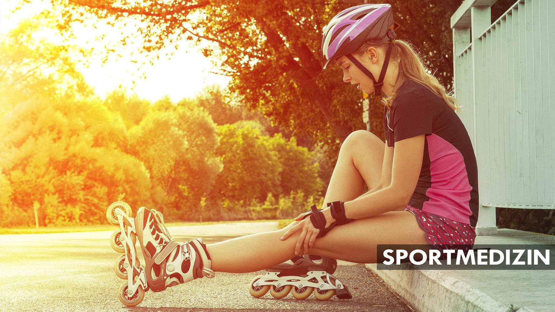 Sportovní žena na kolečkových bruslích sedí na obrubníku a drží si koleno